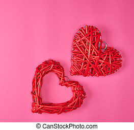 two wicker red hearts on a pink background