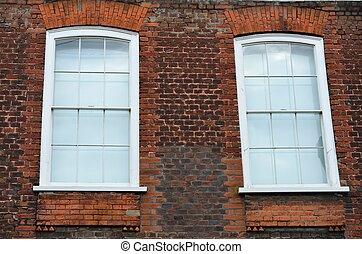 Two windows in brick wall