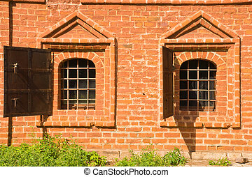 windows of old brick manor house in the park