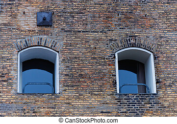 Two windows on brick wall