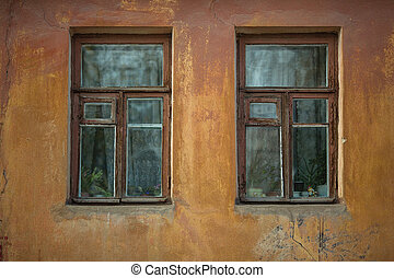 Two windows on the facade of an old stone house.