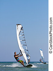 Two windsurfers in action - Front view of two windsurfers in...