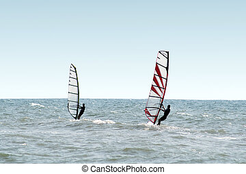 Two windsurfers on waves of a sea