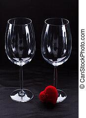 Two wine glasses on dark background.