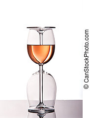 Two wine glasses with rose wine standing on reflective...