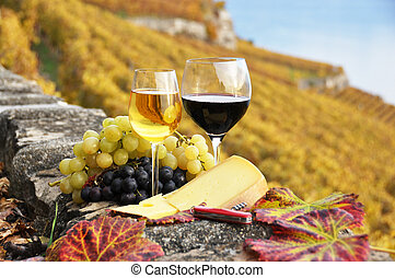 Two wineglasses, cheese and grapes on the terrace of ...
