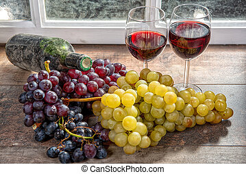 two wineglasses, red and white grapes with bottle of red wine