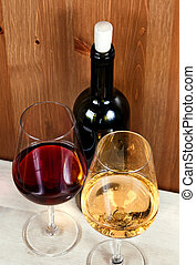 two wineglasses with red wine and white wine and a bottle of wine