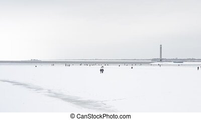 Two winter fishermen walking toward a large group of anglers