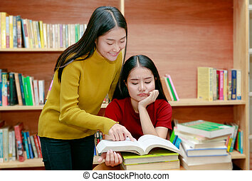 Two woman Asian students reading books In university library