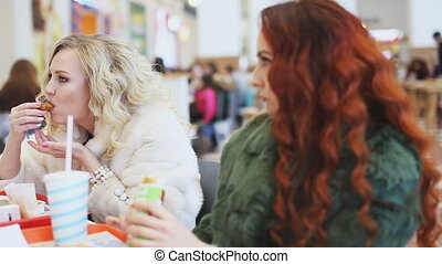 two woman eating junk food