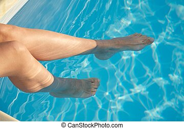 two woman feet in blue pool