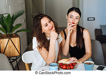 Two woman friends breakfast in the kitchen