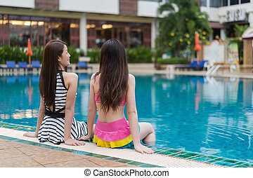 two woman friends sitting on the edge of swimming pool