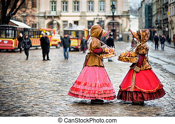 two woman in traditional clothes standing in the square in...