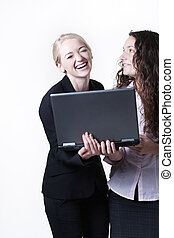 two woman  looking at computer screen