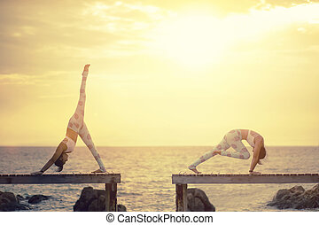 two woman playing yoga pose on wooden pier against sun rising over sea beach
