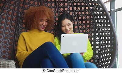 Two woman relaxing in the swing, and browsing social media. African american and asian woman, multiracial friendship concept. High quality 4k footage