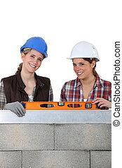 Two woman stood by wall holding spirit level