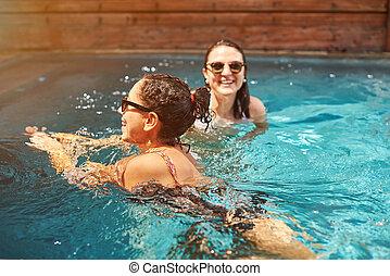 Two woman swimming in pool