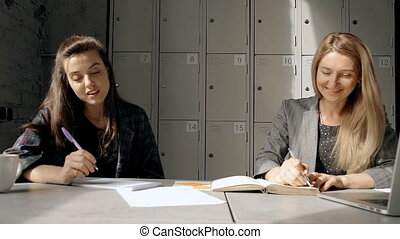 Two woman talking and making notes for seminar - Attractive...