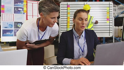 Two woman talking at a desk in a warehouse 4k