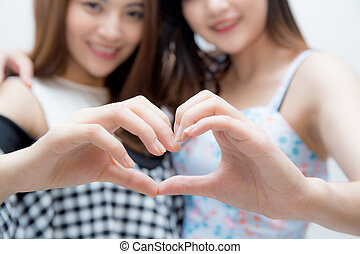 Two woman twins showing heart shape with hands closeup.