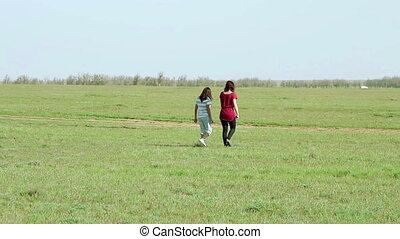 Two woman walking in the meadow