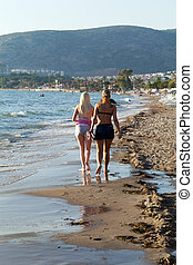Two woman walking on the beach