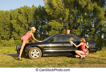 two woman washing the car