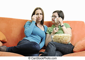 two woman watching television