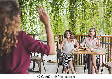 two woman waving hands to their friends
