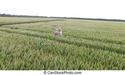 Two woman with blonde hair in a red and blue dress standing in an embrace in the field with wheat.