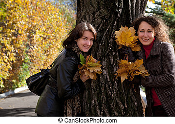 Two woman with bouquets of maple leaves near big tree