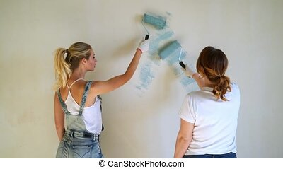 Two woman workers using roller to paint the walls in the...