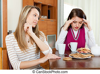 Two women after conflict at table