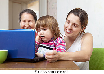 Two women and child buying online with laptop