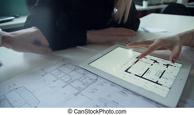 Two women and man discuss architectural project in office using laptop.
