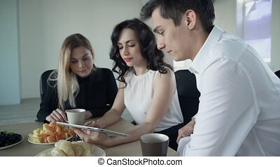 Two women and man have coffee break watching video on laptop.