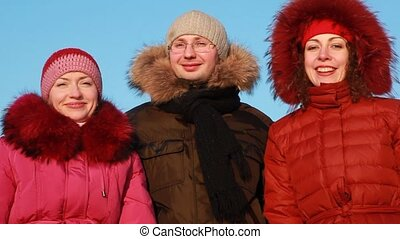 Two women and man standing outdoors at winter