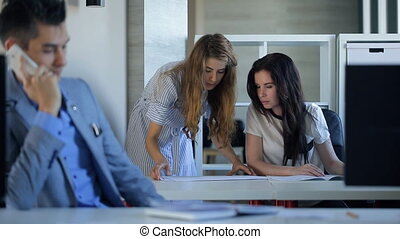 Two women are discussing blueprints sitting in office.
