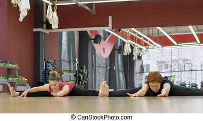 Two women are having yoga training in modern gym with mirror on the wall, slow motion.