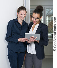 Two women are looking at a tablet