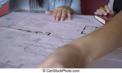 Two women are looking at blueprint, sitting in modern office.