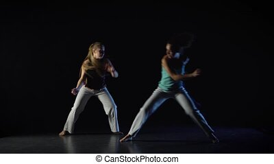 Two women are performing martial art of capoeira. - Two...