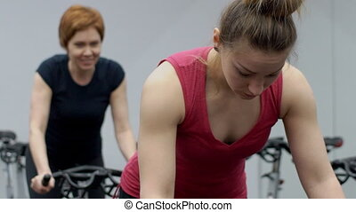 Two women are practicing on aerobic machines in sports club....