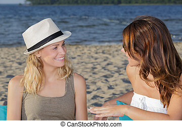 two women are relaxing on the beach together