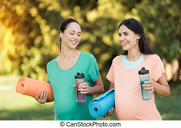 Two women are standing in a park with yoga mats and sports bottles