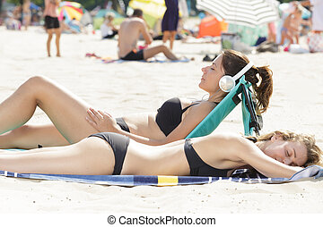 two women are sunbathing at the beach