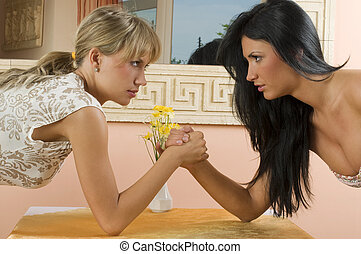 arm wrestling - Two women arm wrestling at work on desk on...